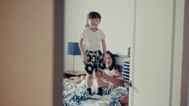 vídeos de stock e filmes b-roll de young taiwanese girl joyfully jumps on the bed on mothers day (slow motion) - east asian ethnicity