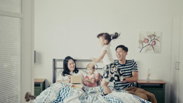 若い台湾の女の子は喜んで母の日にベッドにジャンプ - 建物入口点の映像素材/bロール