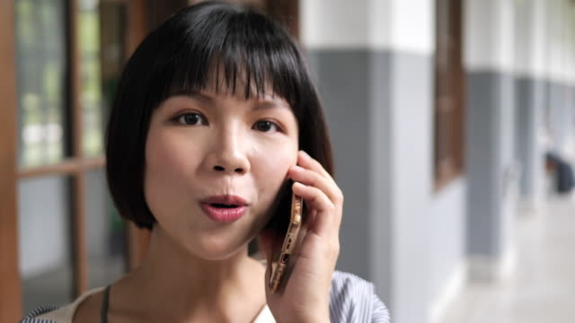 young taiwanese woman talking on the phone. - amicizia tra donne video stock e b–roll