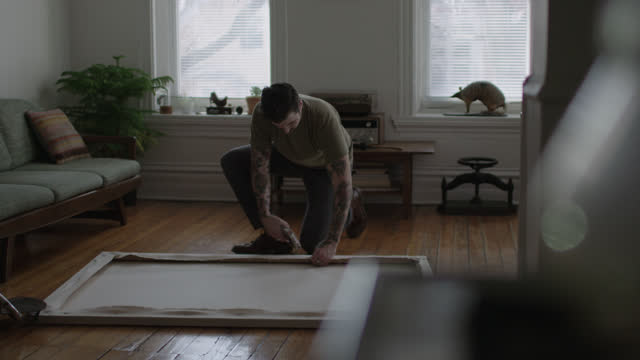 stockvideo's en b-roll-footage met ws slo mo. young tattooed artist uses staple gun to assemble a stretched canvas on apartment floor. - canvas