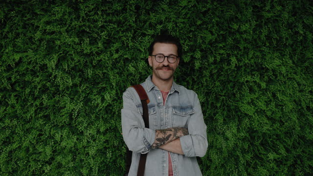 young tattooed hipster posing in front of green wall - in front of stock videos & royalty-free footage