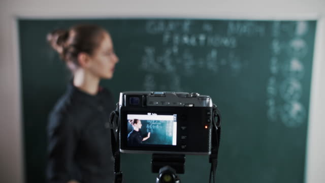 young teacher teaching remotely using camera to stream lesson - insegnante video stock e b–roll