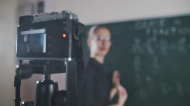 vídeos de stock, filmes e b-roll de jovem professor ensinando remotamente usando câmera para transmitir aula - professor
