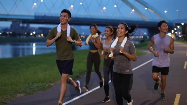 夕暮れ時の若いチームジョギング - jogging点の映像素材/bロール