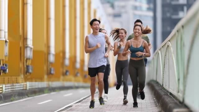 young team jogging on city bridge - chinese ethnicity stock videos & royalty-free footage