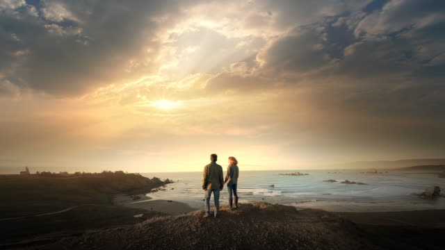Young teen age couple hiking to overlook of Pacific Ocean and sunset, Oregon