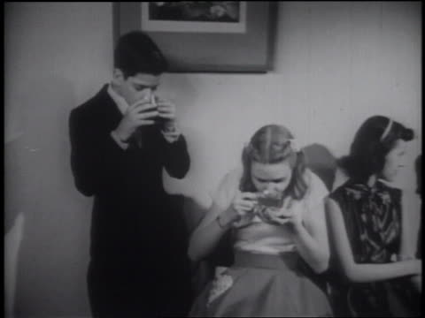 b/w 1953 young teen couple drinking from punch glasses at formal dance + looking at watches - coppia di adolescenti video stock e b–roll