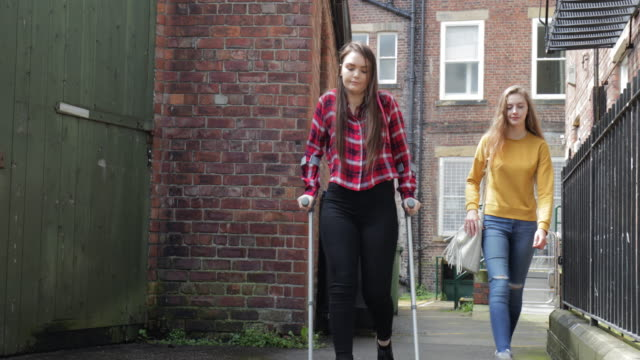Young Teen Girl in Crutches Walking Home