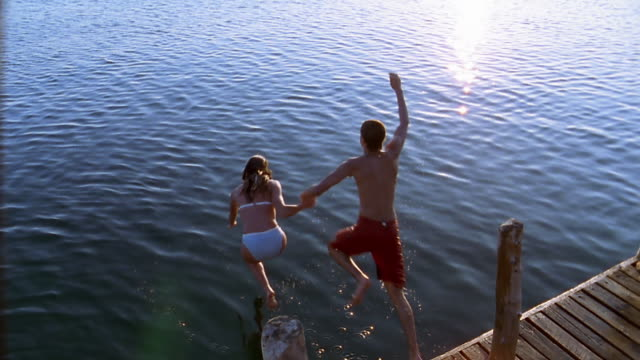 A young teenage couple jumps off a wood dock into the ocean.