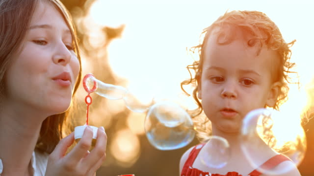 slo mo young teenage girl blowing bubbles for her small toddler sister in setting sun - sapone video stock e b–roll