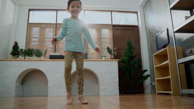 自宅でリビングルームで踊る若い十代の少女 - one teenage girl only点の映像素材/bロール