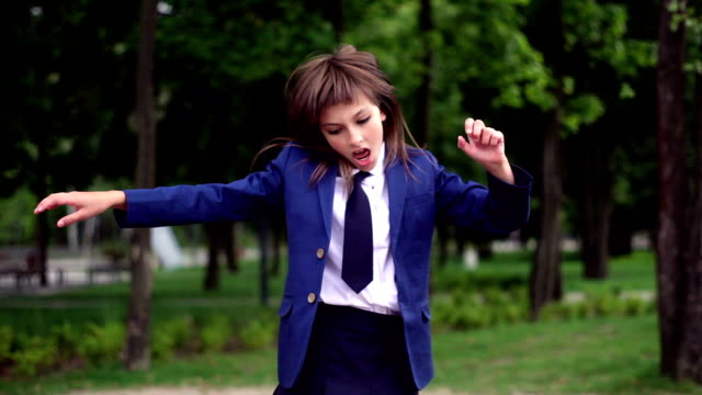 young teenage girl playing jumping in the park area - uniform stock videos & royalty-free footage