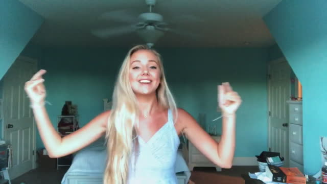 young teenage girl smiling, singing and dancing in her room while video chatting. - teenagers only stock videos & royalty-free footage