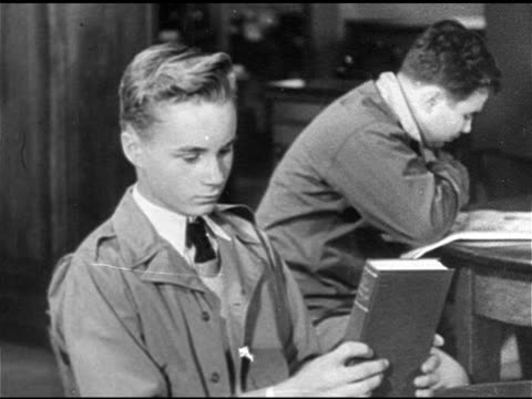 young teenage male finishing closing book, group of people sitting in local library reading books at tables, - 1949 stock videos & royalty-free footage