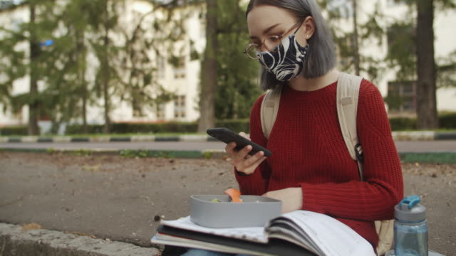 young teenage student walking in reusable protective face mask with smartphone near school on in a college or university campus - university student stock videos & royalty-free footage