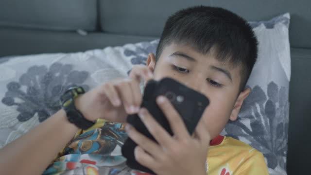 vídeos de stock, filmes e b-roll de uhd/4 k apple prores (hq): jovem adolescente tocando game em smartphone - smart