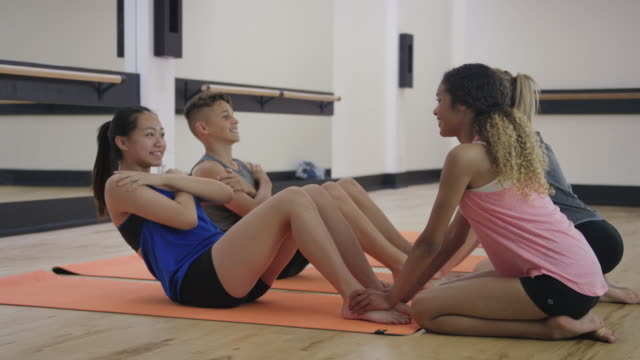Young teenagers doing sit-ups in a studio
