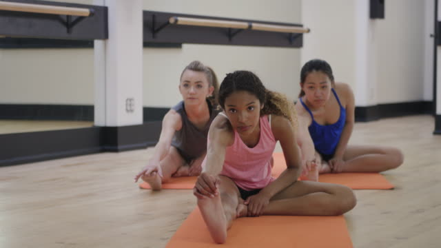 Young teenagers stretching together in a studio