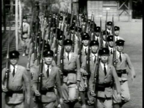 stockvideo's en b-roll-footage met young teens in uniform holding rifles marching - 1943