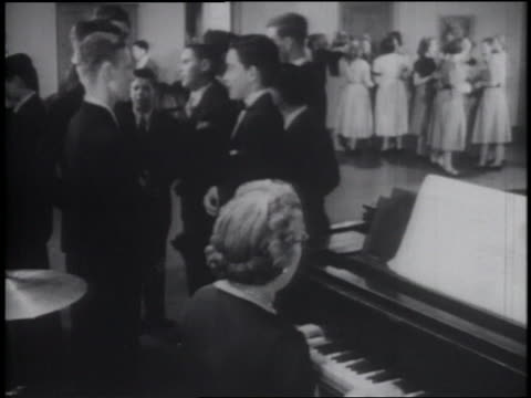 B/W 1953 young teens standing in same-sex groups at formal dance / senior woman playing piano in foreground