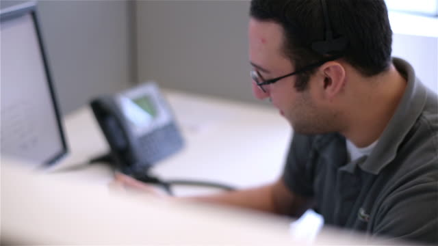 vidéos et rushes de young telemarketer with headset pitches to customer - cool