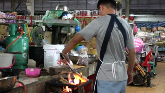 young thai man cocking on fire at mae hong son's morning market in northern thailand - bancarella video stock e b–roll