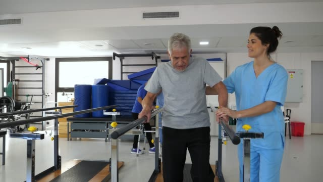 young therapist giving her senior patient instructions while he is walking using the parallel bars - clinica medica video stock e b–roll