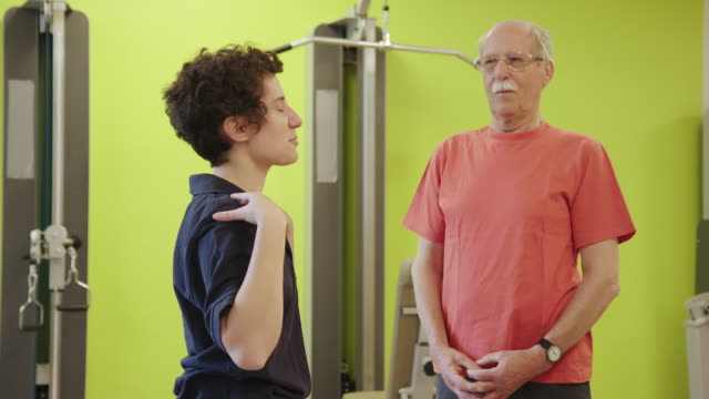 young therapist showing exercise to senior patient - medical examination room stock videos & royalty-free footage