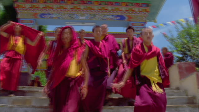Young Tibetan monks in red and yellow robes walk down a staircase near the entrance of a temple. Available in HD.