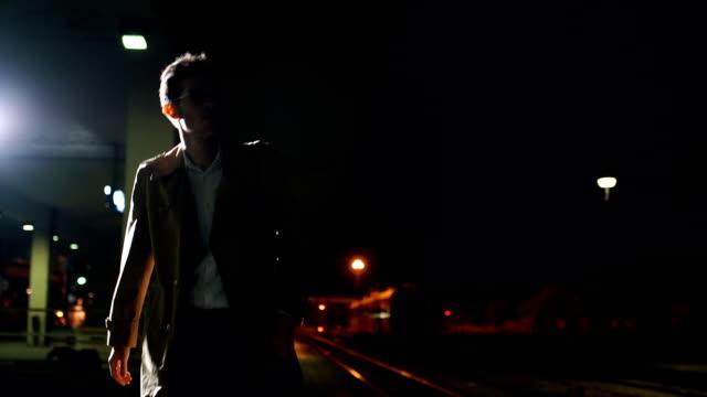 若い疲れて駅の上を歩く男