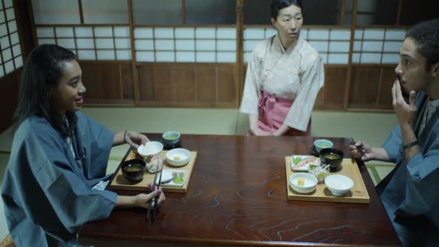vídeos de stock, filmes e b-roll de pares novos do turista que comem no ryokan atendido por hostess - washitsu