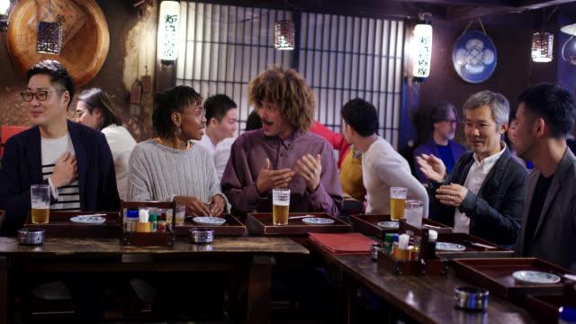 日本の居酒屋で楽しむ若い観光客のカップル - 居酒屋点の映像素材/bロール