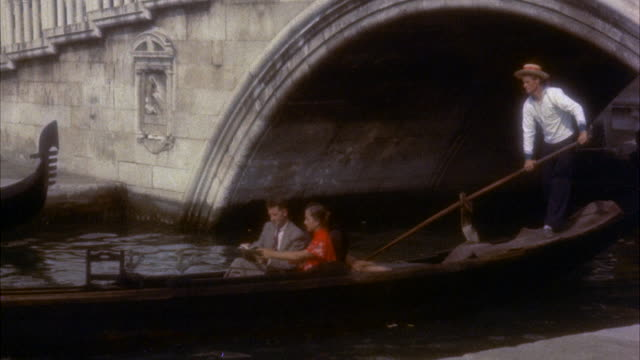 ms young tourist couple in gondola from under bridge / venice, italy - anno 1954 video stock e b–roll