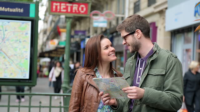 Young tourist couple look at map outside a Paris metro station and decide which way to go.