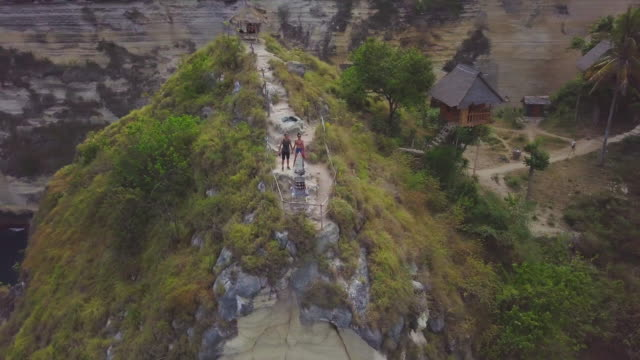 young tourist couple on top of a cliff on nusa penida coastline - indonesia travel stock videos & royalty-free footage