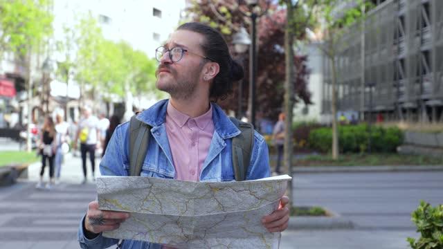 vidéos et rushes de jeune touriste regardant la carte de ville et explorant la ville - échappée belle