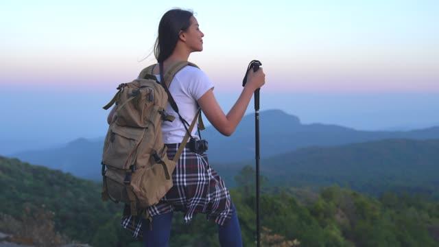 vídeos de stock, filmes e b-roll de a mulher nova do turista está caminhando na parte superior da montagem e olhando uma paisagem bonita. - mochila bolsa