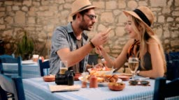 Young tourists couple eating lunch at traditional Greek tavern