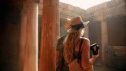 Young tourists couple in Greece taking photos of ancient columns