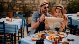 Young tourists couple reading map at traditional Greek restaurant