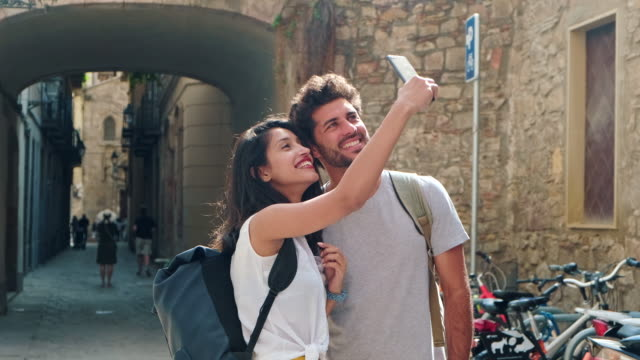 vídeos de stock e filmes b-roll de young tourists taking selfie with smart phone in barcelona - perto
