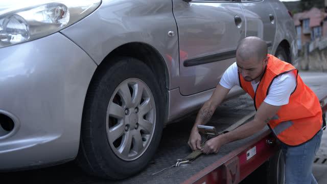 vídeos y material grabado en eventos de stock de joven trabajador de la grúa que asegura el coche en la plataforma - grúa
