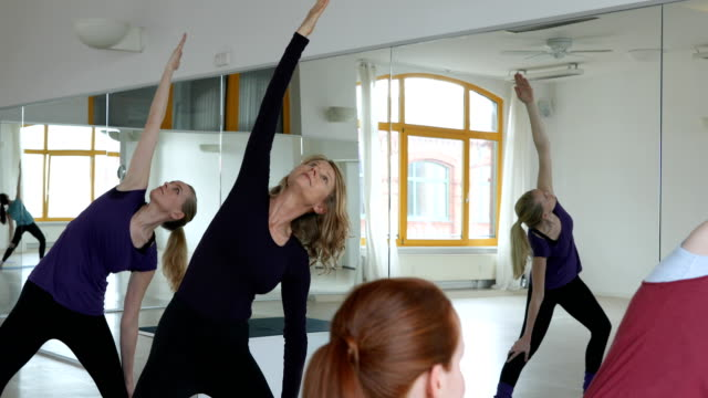 Young trainer instructing women in yoga class