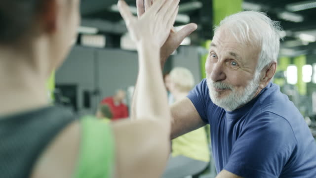 stockvideo's en b-roll-footage met jonge trainer met senior client op sportschool - oud