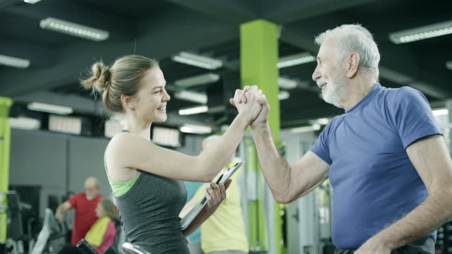 young trainer with senior client at gym - uomini anziani video stock e b–roll