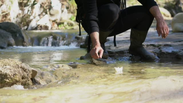 Young travel man with Paper Boats in mountain river