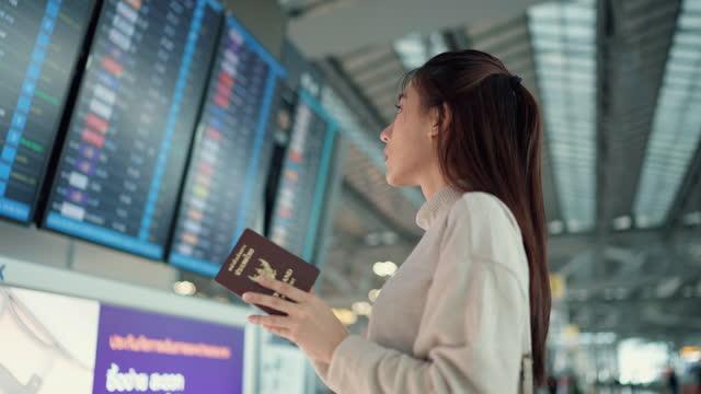 vidéos et rushes de jeune femme de voyageur vérifiant l'heure d'embarquement à l'horaire numérique - avion de tourisme