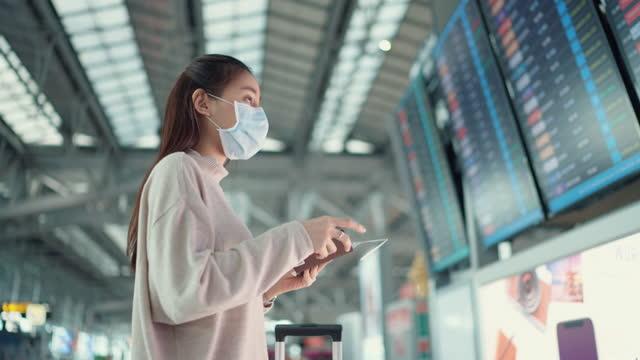 vídeos y material grabado en eventos de stock de mujer joven viajera usa máscara quirúrgica comprobando el tiempo de embarque en el horario digital - tabla de llegadas y salidas