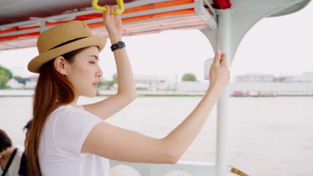 young travelers are using mobile camera views during a boat ride across the river to wat arun.asian woman enjoying for landmark of bangkok wat arun in bangkok city - beautiful people stock videos & royalty-free footage