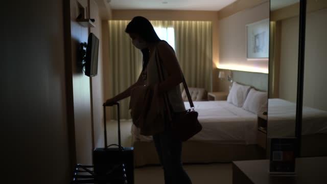 vídeos de stock, filmes e b-roll de jovem viajante chega ao hotel usando máscara facial - turista